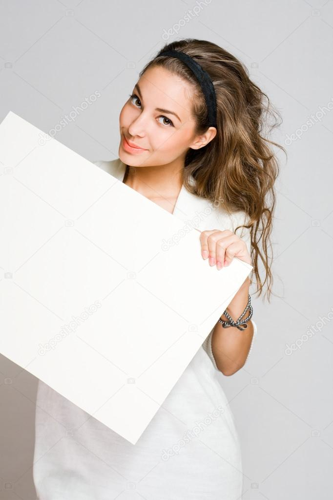 Freindly young brunette beauty holding white blank banner.  Stock Photo #14784299