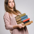 Young brunette with large pile of books. — Stock Photo #19213617