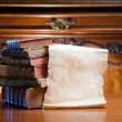 Old paper scroll with antique books. — Stock Photo