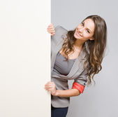 Young businesswoman with large blank banner. — Stock Photo