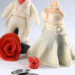 Stock Photo: Wedding Rings and Miniature Couple Fondant Cake