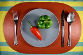 Green and Red Bell Pepper on a Plate — Stock Photo