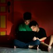 Young asian kids, brothers or siblings, with a laptop computer in a living room — Stock Photo #45136361
