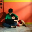 Young asian kids, brothers or siblings, with a laptop computer in a living room — Stock Photo #45136399