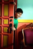 Young asian teen peeking and sneaking in into a living room — Stock Photo