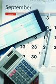 Calendar, checkbook, calculator, money and a ballpen — Стоковое фото