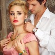 Young mputs on jewelry on beautiful woman — Stock Photo #13914105