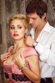 Young man puts on jewelry on beautiful woman — Stock Photo