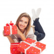 Young woman holding gift, lies with three gifts is isolated on w — Stock Photo