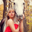 Stock Photo: Young woman taking care of her horse