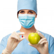 Young doctor holding pill and apple — Stock Photo
