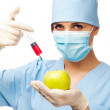 Young doctor with syringe and apple — Stock Photo