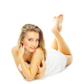 Young woman in towel terry feet up lies on floor — Stock Photo
