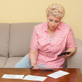 Blond senior calculating her debts — Stock Photo