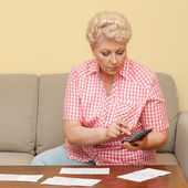 Beautiful senior calculating her debts — Stock Photo