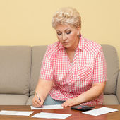 Senior calculating her debts and write it — Stock Photo