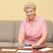 Happy senior calculating her debts — Stock Photo