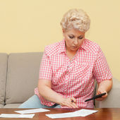 Senior calculating her debts — Stock Photo