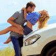 Young mkisses womsitting by car against sea — Stock Photo #29374391
