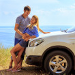Young man and woman in stand at car against sea — Stock Photo