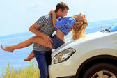 Young man kisses woman sitting by car against sea — Stock Photo