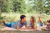 Beautiful couple on picnic, look at each other. — Stock Photo