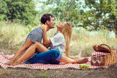 Young couple on picnic, sitting face to fa — Stock Photo