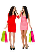 Two young shopping women talking by phone — Stock Photo
