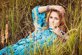 Beautiful blond woman in dress lies on grass — Stock Photo