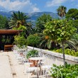Outdoor restaurant with palm trees and mountains on the backgrou — ストック写真