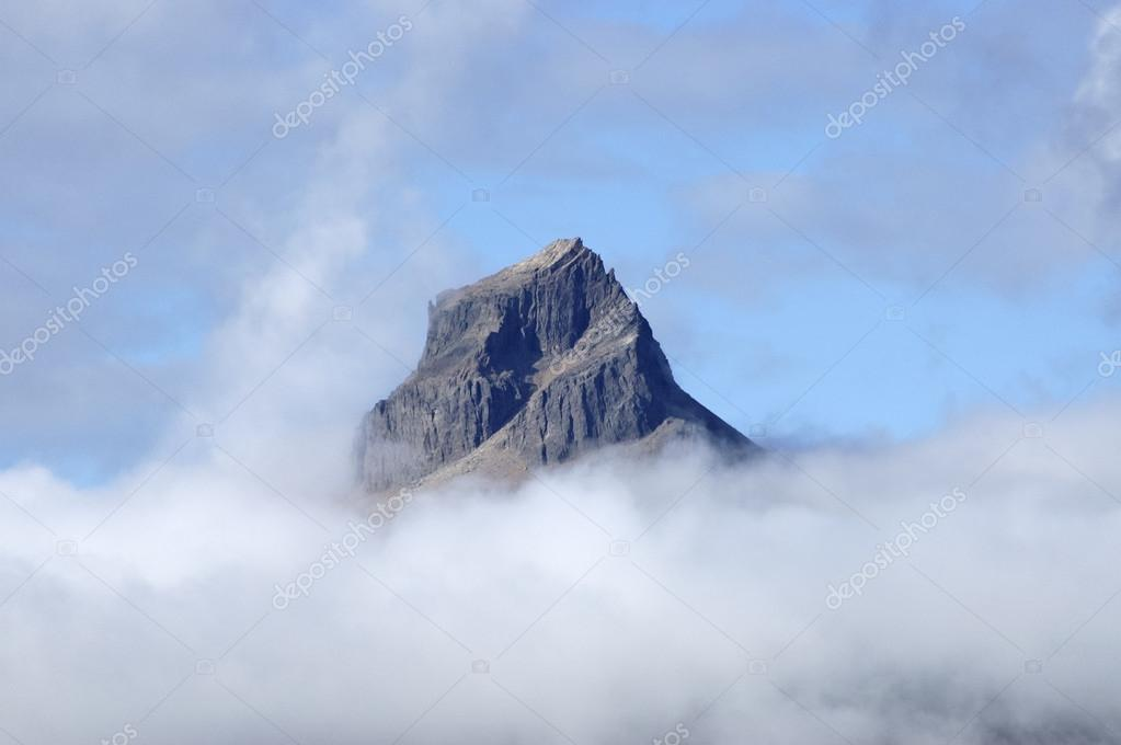 Rocky mountain cliff above clouds in Iceland.  Stock Photo #12851649