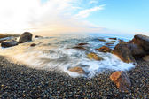 Sunrise on beach with rocks and sea — Stock Photo