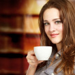 Beautiful Young Women Drinking a Cup of Coffee — Stock Photo #12490746