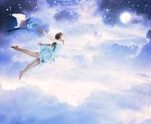 маленькая девочка, летающих в синий ночное небо — Стоковое фото