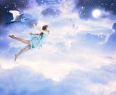 Little girl flying into the blue night sky — Stockfoto