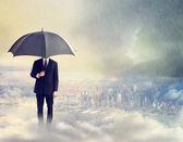 Man met paraplu boven de stad — Stockfoto