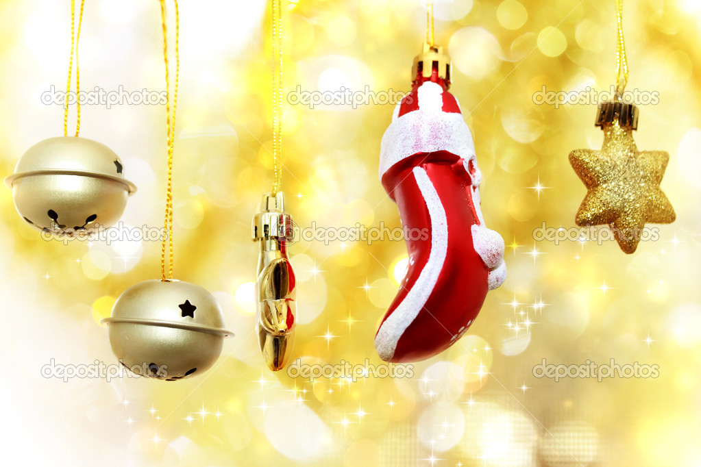 Christmas bells, glove and stars hanging over golden bokeh background  Stock Photo #15636911