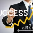 Businessman writing success with a rising arrow — Stockfoto