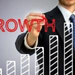 bir çubuk grafik üzerinde büyüme yazma işadamı — Stockfoto