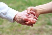 Seniors et jeunes femmes main dans la main — Photo