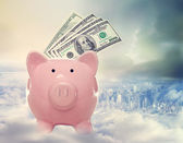 Piggy bank with hundred dollar bills above the city — Stock Photo