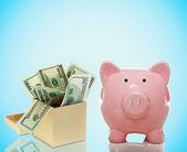 Piggy bank with a box of bills — Stock Photo