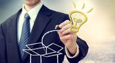 Business man with idea light bulb coming 'out of the box' — Zdjęcie stockowe