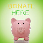 Piggy bank with donate here text — Stock Photo