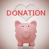 Piggy bank with heart and donation text — Stock Photo