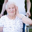 Stockfoto: Happy senior lady in wheelchair