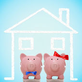 Piggy bank couple with dream home — Stock Photo