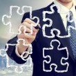 Businessman with puzzle pieces — Stockfoto