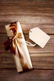 Gift box on a rustic wooden table with a blank tag — Foto de Stock