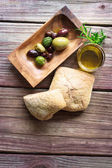 Pickled olives with bread and olive oil on a rustic table — Stock Photo